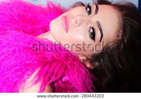 Portrait of beautiful fashionable young woman with bright make up lying and looking sexy in pink clothes with long hair, horizontal picture - stock photo