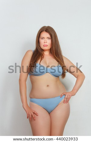 Portrait of beautiful fat woman in lingerie or underwear posing in studio. Red haired lady posing with her hand on hip. - stock photo
