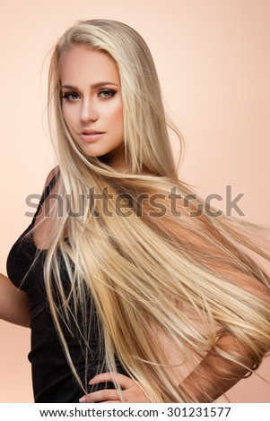 Portrait of beautiful female model with long hair on beige background - stock photo