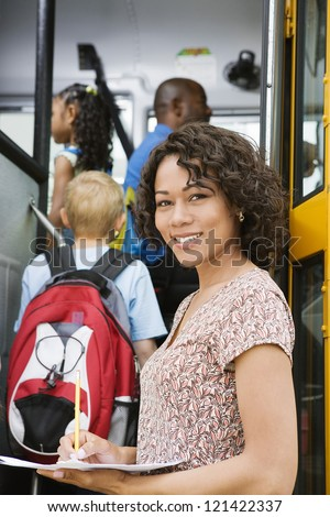 Portrait of beautiful female teacher writing down something on paper while students boarding school bus - stock photo