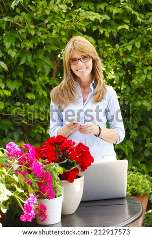 Portrait of beautiful flower shop owner working on laptop. Small business.  - stock photo