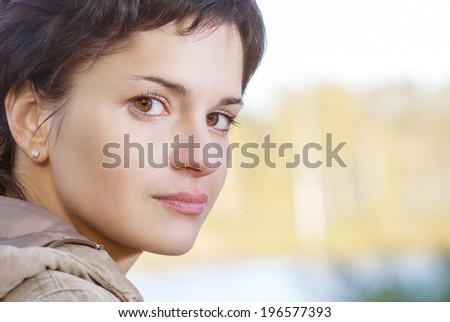 Portrait of beautiful girl against trees - stock photo