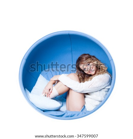 portrait of  beautiful girl at the circle,  woman in  warm sweater and socks sits comfortably,  chair with pillows - stock photo