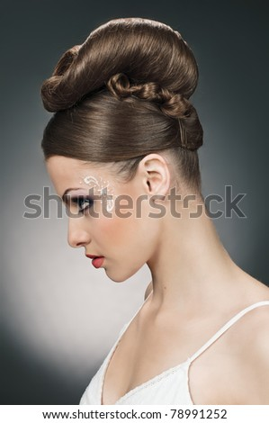 portrait of beautiful girl bride with coiffure and make up on grey - stock photo
