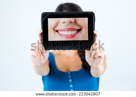 Portrait of beautiful girl holding a picture of a mouth smiling. - stock photo