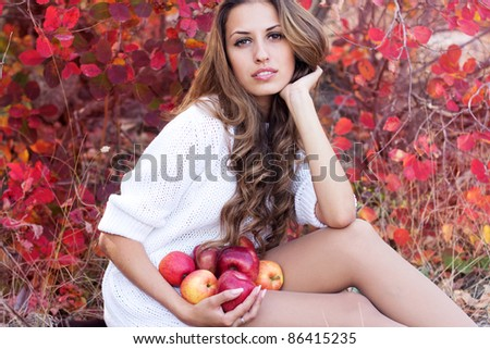 portrait of beautiful girl in autumn leaves. Apple in hand. - stock photo