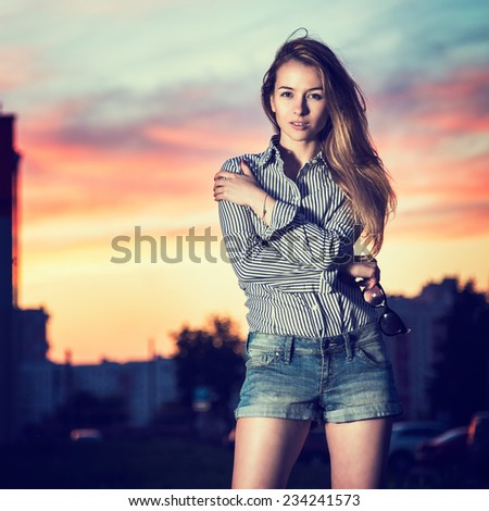 Portrait of Beautiful Girl in Evening City Embracing Herself. Urban Fashion Concept. Copy Space. - stock photo