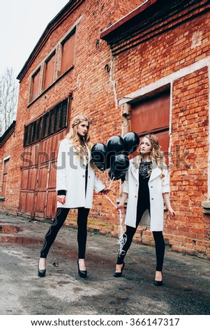 Portrait of beautiful girl in fashionable clothes with black balloons - stock photo