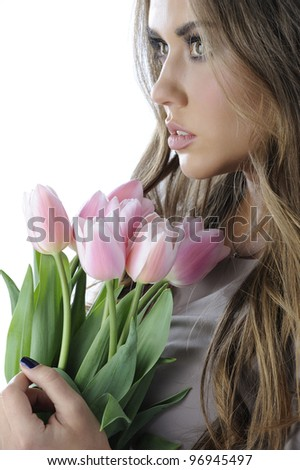 Portrait of beautiful girl in gray dress with a bouquet of pink tulips - stock photo