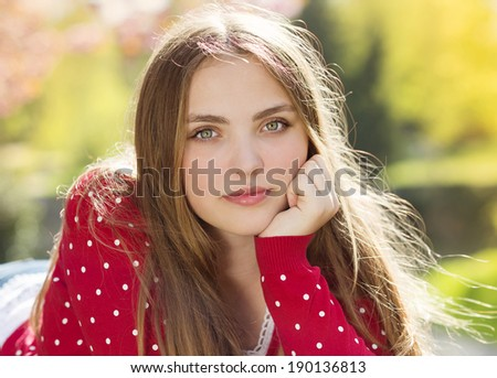 Portrait of beautiful girl in red cardigan in green prak - stock photo