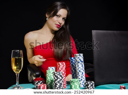 Portrait of beautiful girl in red dress while playing poker online - stock photo
