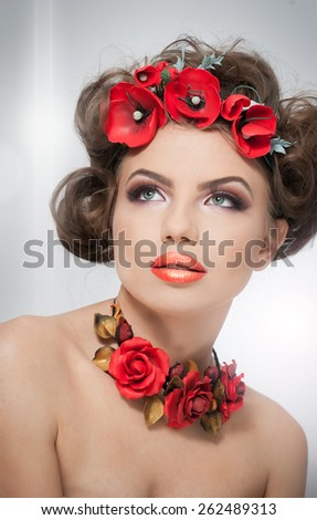 Portrait of beautiful girl in studio with red flowers in her hair and red roses around her neck. Young woman with makeup and bright flowers as accessories. Creative hairstyle and makeup, studio - stock photo