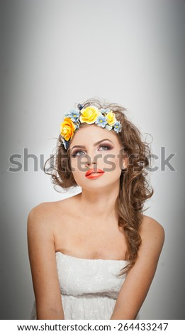 Portrait of beautiful girl in studio with yellow roses in her hair and naked shoulders. Sexy young woman with professional makeup and bright flowers. Creative hairstyle and makeup, studio shot - stock photo