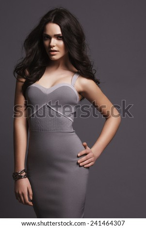 Portrait of beautiful girl in the studio on a gray background in dress  - stock photo