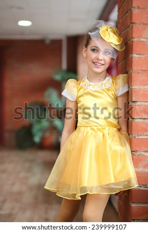 Portrait of beautiful girl in yellow satin dress near brick wall - stock photo