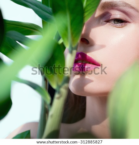 Portrait of beautiful girl looking out of the greens - stock photo