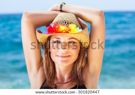Portrait of beautiful girl on the beach, wearing sun hat with colorful flowers decoration, having fun on beach party, happy summer holidays - stock photo