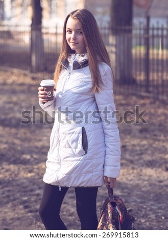 Portrait of beautiful girl schoolgirl brunette holding a cup of coffee in the fall or spring day, smiling happy. Holding a beautiful and fashionable backpack. - stock photo
