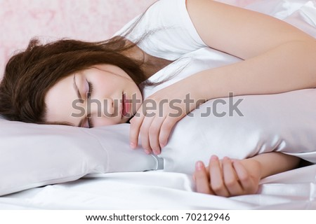 portrait of beautiful girl sleeping in bedroom on linen - stock photo