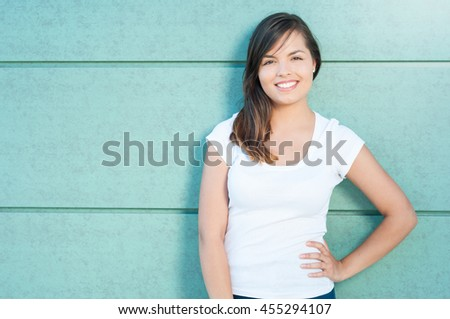 Portrait of beautiful girl smiling with hand on waist outside on green wall with copy text space - stock photo