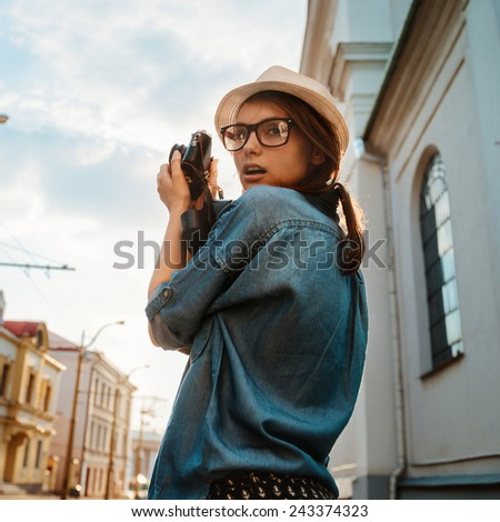 portrait of beautiful girl tourist photographing the old streets of the city outdoor - stock photo