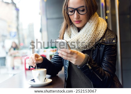 Portrait of beautiful girl using her mobile phone in cafe. - stock photo