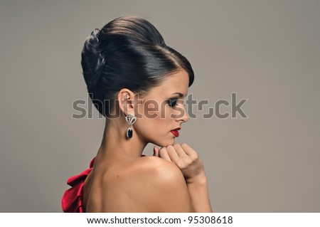 portrait of beautiful girl with elegant coiffure and red dress on grey - stock photo