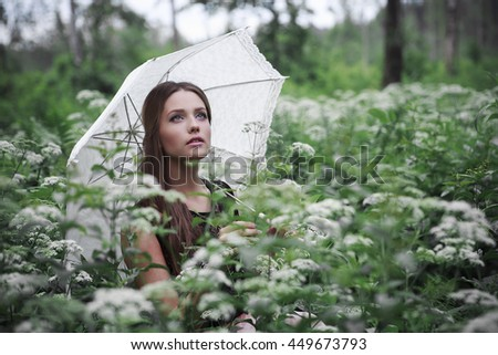 Portrait of beautiful girl with umbrella in nature and white flowers - stock photo