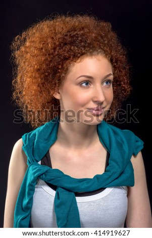 portrait of beautiful gorgeous female fashion model with red curly hair in white shirt with a jacket draped over his shoulders, studio shooting, on black background - stock photo
