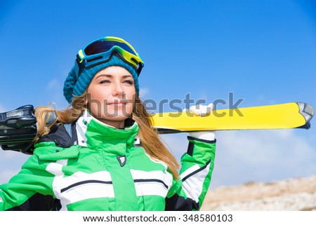 Portrait of beautiful gorgeous skier woman, wearing sportive clothes and holding in hands ski, active wintertime vacation - stock photo