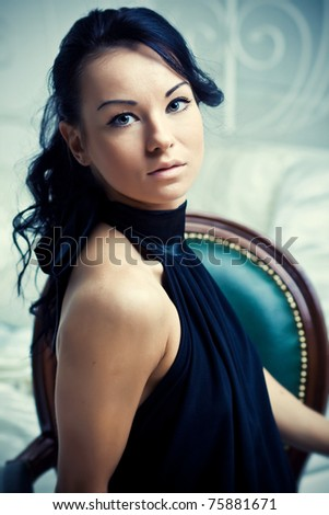 Portrait of beautiful handsome woman in black dress - stock photo