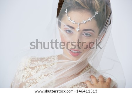 Portrait of beautiful happy bride posing with veil covering her face. Studio shot. - stock photo