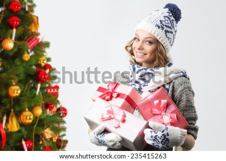 Portrait of beautiful happy girl in sweater hat and mittens with boxes of Christmas gifts against the background of the Christmas tree, Christmas holiday and New Year. - stock photo