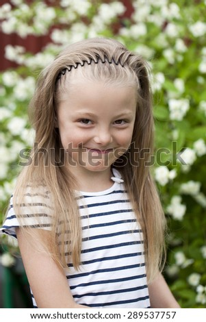 Portrait of beautiful happy little girl, against background of summer park - stock photo