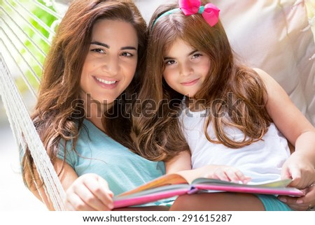 Portrait of beautiful happy mother with cute little daughter sitting on backyard in hammock and reading interesting book, nice lovely family - stock photo