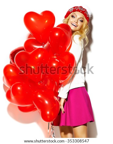 portrait of beautiful happy sweet cute smiling blonde woman girl in casual hipster clothes, in pink skirt and winter warm beanie with red heart balloons in hands - stock photo