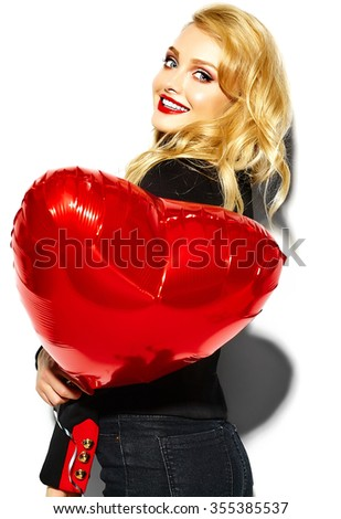 portrait of beautiful happy sweet smiling blonde woman girl holding in her hands red heart balloon in casual black hipster clothes with red lips - stock photo