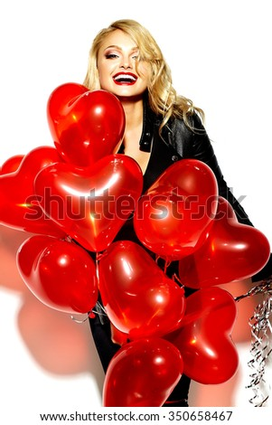 portrait of beautiful happy sweet smiling blonde woman girl holding in her hands red heart balloons in casual black hipster clothes - stock photo