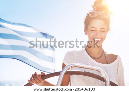 Portrait of beautiful happy woman driving sailboat, Greek flag on the deck, traveling along Mediterranean sea, active summer vacation - stock photo