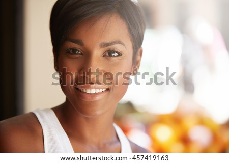 Portrait of beautiful happy young black model with short pixie hairstyle and healthy clean skin looking and smiling at the camera with cheerful expression, showing her white teeth, posing outdoors - stock photo