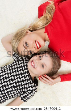Portrait of beautiful happy young woman and girl lying on beige cover. Close up. - stock photo