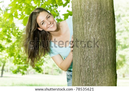 Portrait of beautiful happy young woman in park. - stock photo