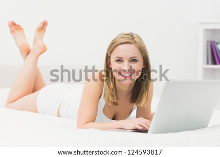 Portrait of beautiful happy young woman lying in bed and using laptop at home - stock photo