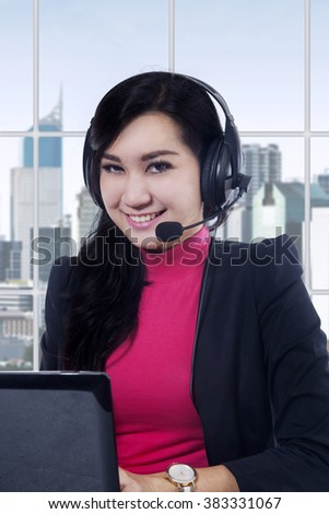 Portrait of beautiful helpdesk operator working in the office with laptop and headphones, smiling at the camera - stock photo