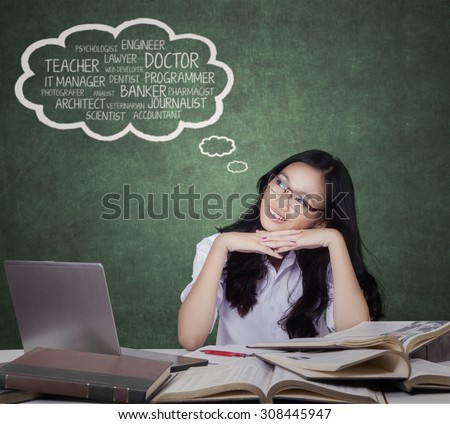 Portrait of beautiful high school student sitting in the classroom while imagine future jobs - stock photo