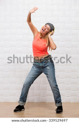 Portrait of beautiful hipster girl in full length dancing modern dances in studio while listening to the music. Happy lady singing and dancing. - stock photo
