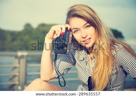 Portrait of Beautiful Hipster Girl with Vintage Camera. Modern Youth Lifestyle Concept. Toned Photo with Copy Space. - stock photo
