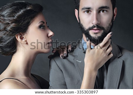 Portrait of beautiful lady with handsome guy in suit. Young couple is hugging each other. Girl and boy with attractive faces indoors in passionate pose. Beauty woman with hairstyle. Man with a beard - stock photo