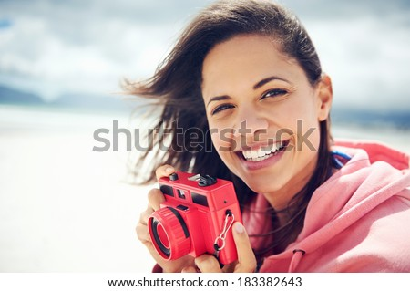 Portrait of beautiful Latino woman with retro hipster camera having fun at the beach - stock photo