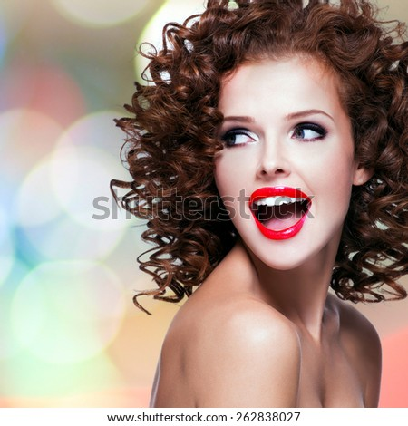 Portrait of beautiful laughing woman with brunette curly hair and bright make up looking at camera. - stock photo